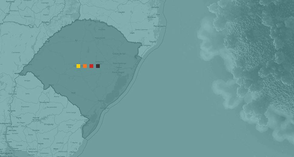 Imagem de um mapa, destacando o mapa do estado do Rio Grande do Sul. No centro, tem ícones quadrados nas cores amarelo, laranja, vermelho e preto.