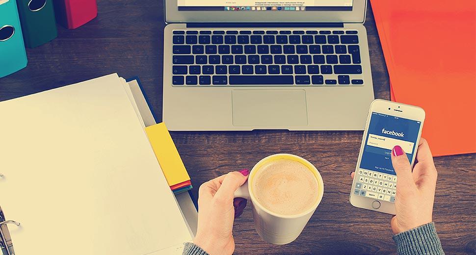 Foto de uma mesa de trabalho. Sobre ela tem um notebook, uma pasta, e as mãos de uma mulher segurando uma xícara de café e um smartphone; na tela do smartphone aparece a página do Facebook.