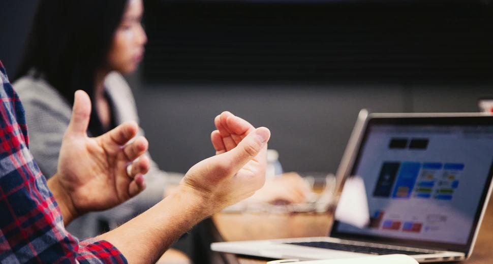 Foto de um homem em uma mesa de trabalho, em frente ao computador, participando de uma reunião virtual. Aparecem as mãos dele gesticulando.