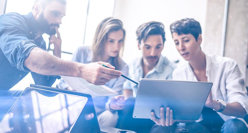 Na imagem tem 4 pessoas em um ambiente de escritório, 3 sentadas e uma em pé, olhando atentamente para um notebook.