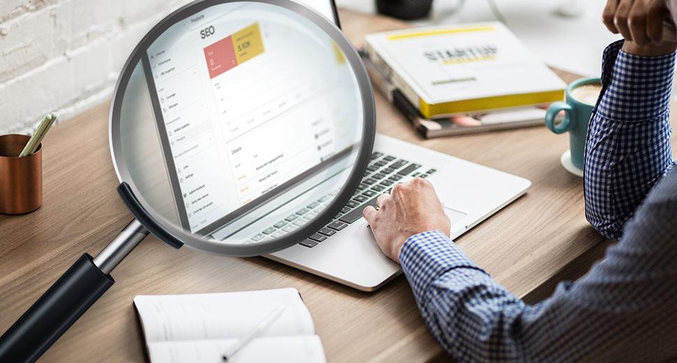 Imagem de um jovem trabalhando em um computador, Na tela aparecem dados de SEO de um site, apliados pela imagem de uma lupa à frente.