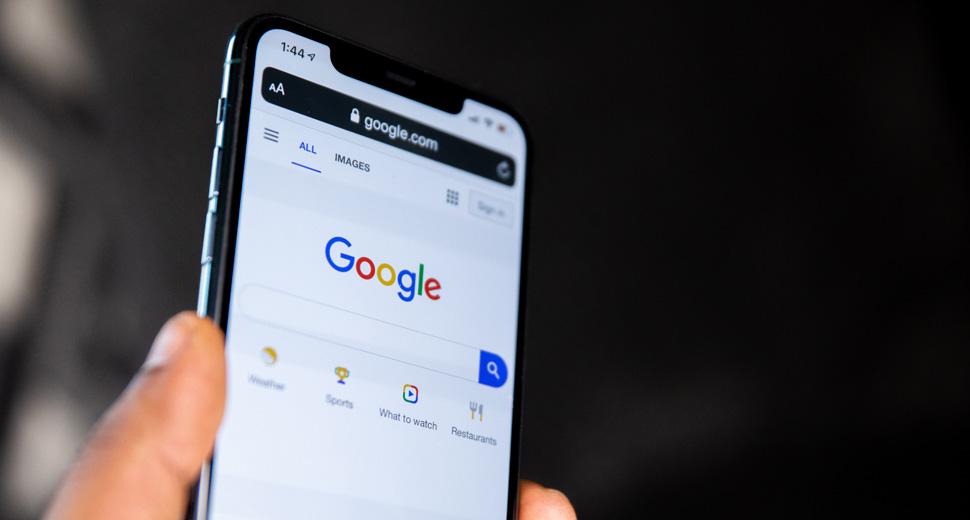 Foto de uma mão segurando um celular. Na tela do celular aparece a página de buscas do Google.