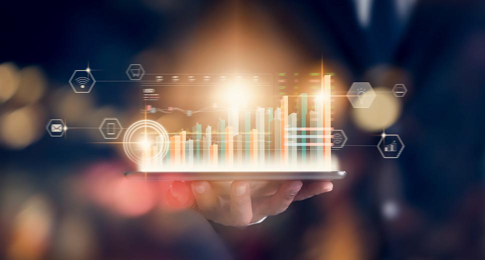 Foto de uma mão segurando um tablet. Da tela do tablet, saem diversos gráficos mostrando indicadores de campanhas digitais.