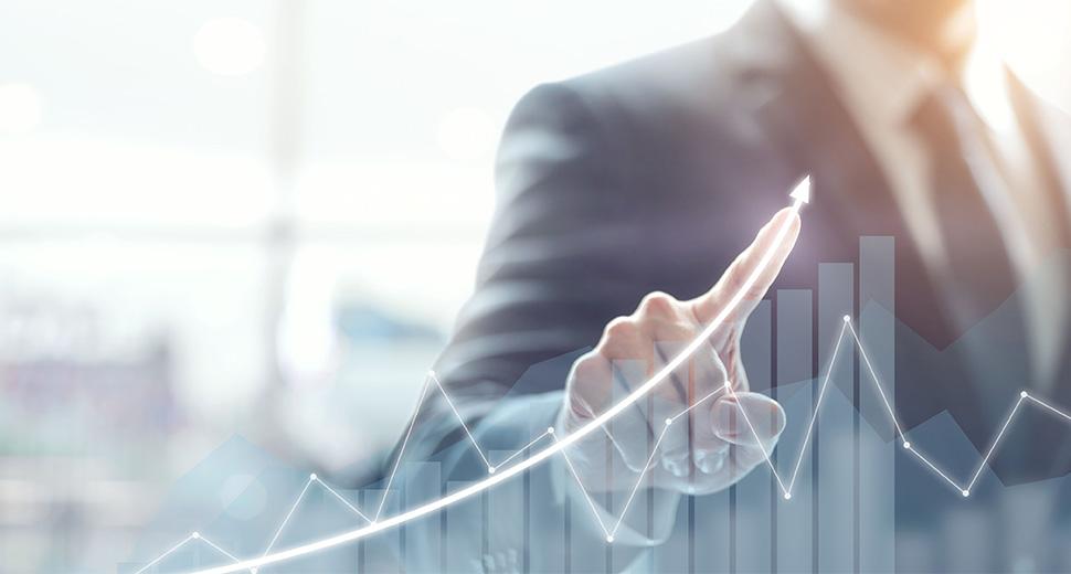 Foto de um homem interagindo com os dados de um gráfico. No gráfico, aparecem linhas e colunas. Ele aponta com o dedo indicador para uma curva ascendente, indicando crescimento.