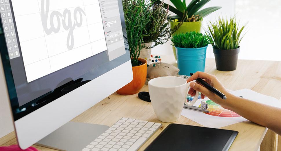 """Foto de uma mesa de trabalho. Sobre ela tem um computador, uma mesa digital, papeis, pequenos vasos de plantas e a mão de uma pessoa pegando uma xícara. Na tela do computador lê-se """"logo""""."""