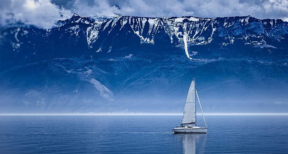 Foto de um barco à vela em alto mar, passando ao lado de uma onda gigante se formando.
