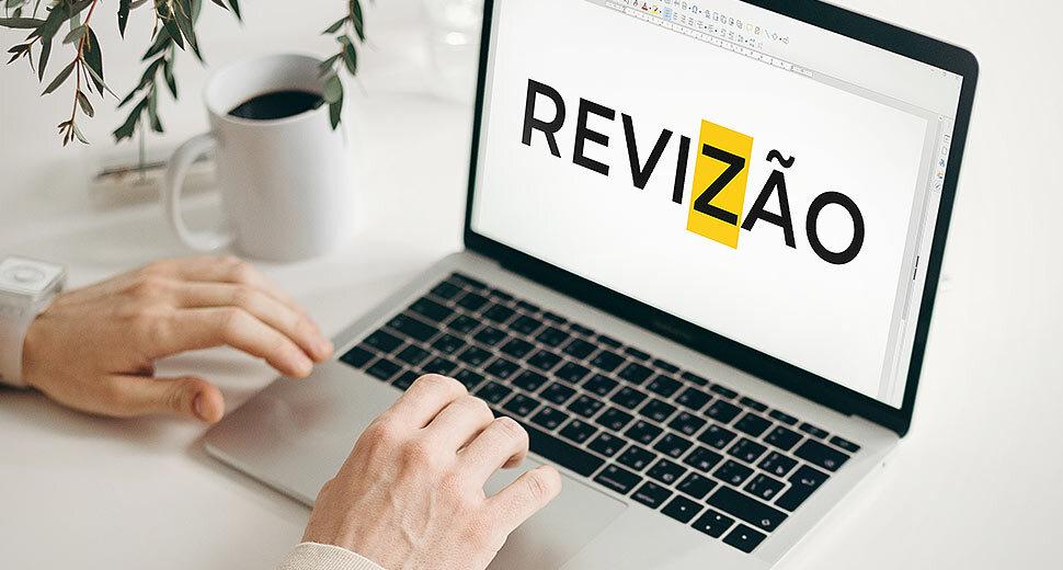 Foto de um notebook sobre uma mesa, e as mãos de uma pessoa teclando nele. Na tela do notebook, aparece a palavra revisão escrita errada, com a letra Z no lugar da letra S.