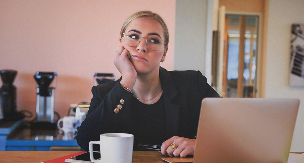 Foto de uma mulher jovem. Ela está sentada em uma mesa olhando para a tela de um notebook, pensativa.