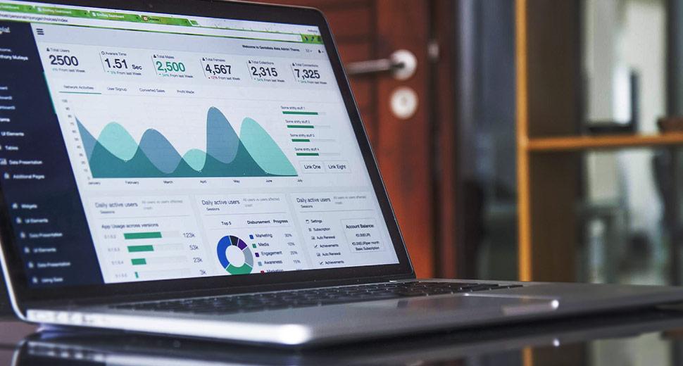 Foto de um notebook sobre uma mesa. Na tela, aparecem gráficos que demonstram o tráfego e o comportamento de usuários em um site.