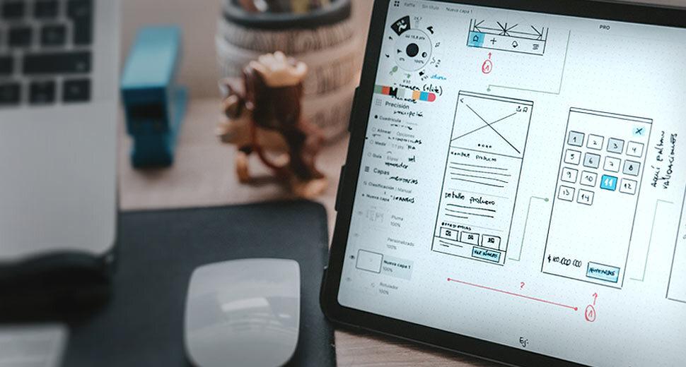 Foto de uma mesa em um ambiente de trabalho. Sobre ela tem um notebook, um mouse e um tablet. Na tela do tablet aparecem imagens de um projeto de UX writing sendo desenhado.