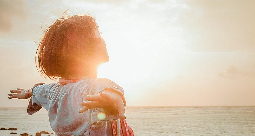 Foto de uma mulher na beira da praia, braços abertos, contemplando o sol!