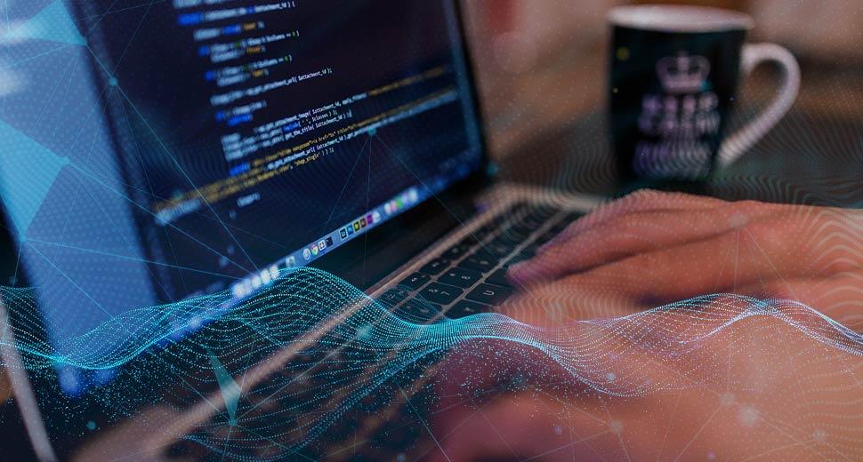 Na foto, aparecem as mãos de um home teclando em um notebook. Sobre a foto, aparece uma trama de luz neon azul, simulando a transmissão de dados.