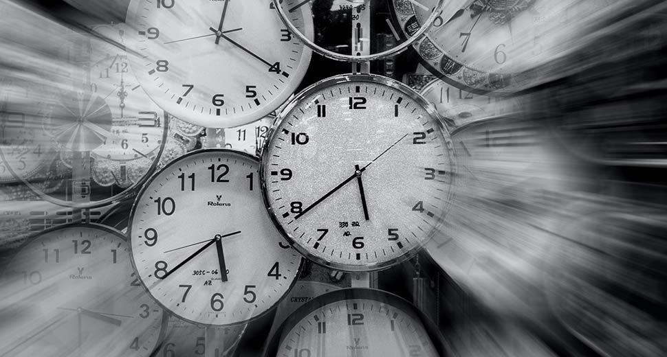 Foto de vários relógios, sobrepostos, marcando horários diferentes. Alguns estão com a imagem desfocada, dando ideia de tempo passando.