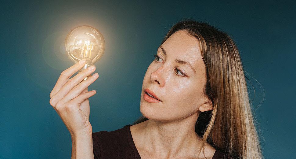 Foto de uma mulher segurando e olhando uma lâmpada acesa.