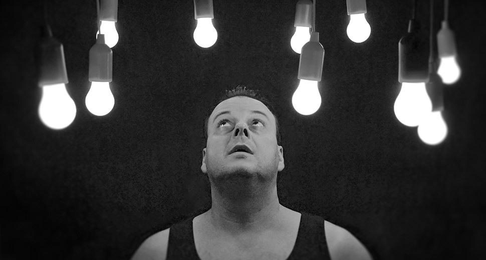 Foto de um homem olhando para cima, onde tem diversas lâmpadas acesas penduradas.