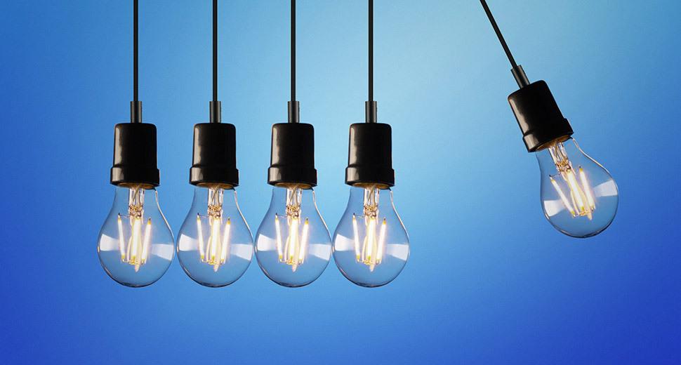 Na imagem aparecem cinco lâmpadas iguais, penduradas lado a lado. Uma delas se distancia das outras.